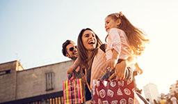 un couple avec leur fille dans les bras et des sacs