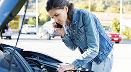 femme qui regarde le moteur de sa voiture