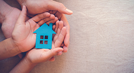 des mains qui protègent une petite maison