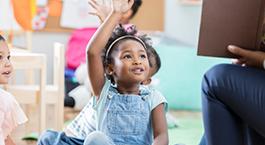 une petite fille à l'école qui lève la main