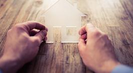 deux mains qui tiennent une petite maison
