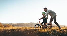 un père qui apprend à son enfant à faire du vélo